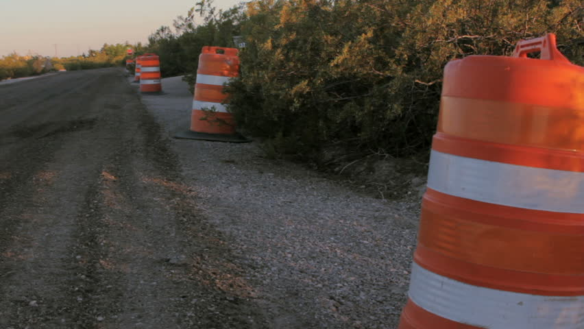 Bright orange traffic drums line the side of fresh road construction. The sun sets over the fresh asphalt. The striped barrels barricade drivers from road construction.   | Shutterstock HD Video #17800186