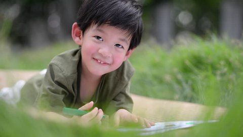 Cute Asian child drawing picture with crayon,outdoors