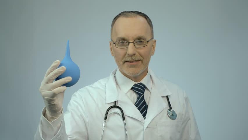 Funny doctor pressing on rectal syringe with smile on face, proctologist joking