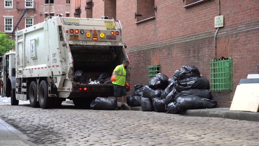 Brooklyn, NY - June 2016: DSNY workers collect trash on a city street. New York Department of Sanitation is responsible for garbage and recycling collection, street cleaning, and snow removal.