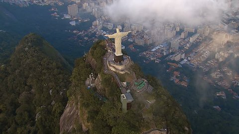 RIO DE JANEIRO, BRAZIL - JUNE 2016: High angle Aerial View of Christ the Redeemer Statue with clouds in Rio de Janeiro, Brazil. View of Christ with people visiting Corcovado Hill.