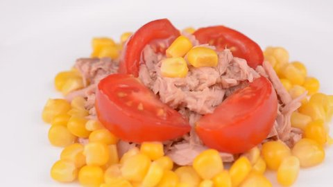 Tuna salad with tuna chunks, tomato pieces and canned corn on white plate rotating