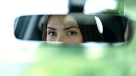 Young beautiful woman looking in rear view mirror