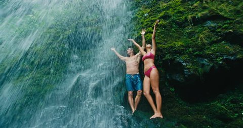 Couple Relaxing Under Waterfall