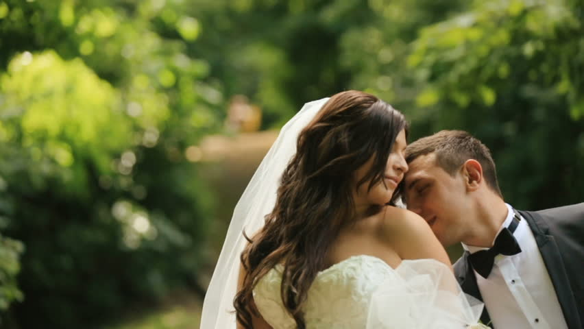 Loving groom kisses shoulder of his charming bride in sunny summer park. Just married couple outdoors #17874346