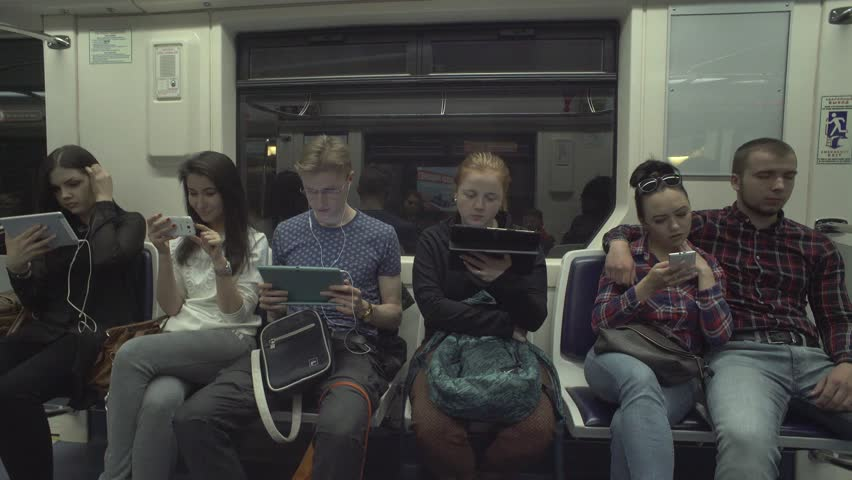 Young people reading news online, using app, texting on gadgetsin metro train | Shutterstock HD Video #17877586