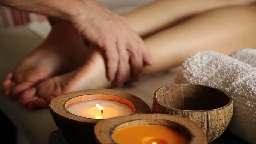 Young woman gets a foot massage in the spa salon. close-up of candles. male hands slide on the female legs