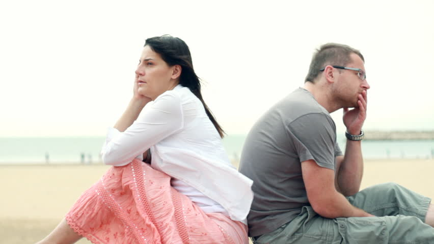 Relationship difficulties, young couple sitting by the beach