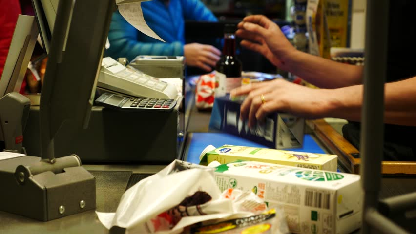hands cashier check out goods line at the supermarket checkout