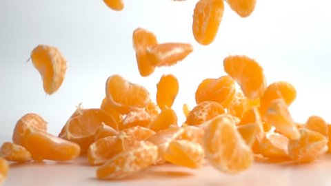 Orange or tangerine slices falling on white background. This video clip was shot in slow motion.
