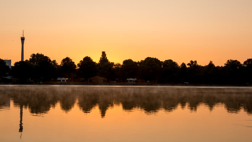 Beautiful sunrise time lapse shot with mist floating across the huge artificial lake Maschsee in Hannover, Germany.    Shutterstock HD Video #17911351
