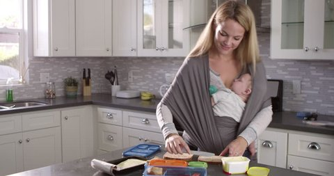 Mum preparing lunchbox while baby sleeps on her in a sling, shot on R3D
