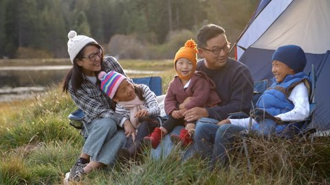 Asian family on a camping trip relaxing outside their tent