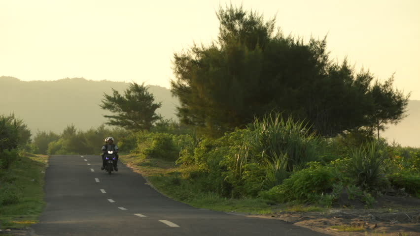 Yogyakarta, Indonesia - May 15, 2015: Unidentified young Indonesian guys riding scooter on empty rural road at sunrise in Java, Indonesia   Shutterstock HD Video #17966446