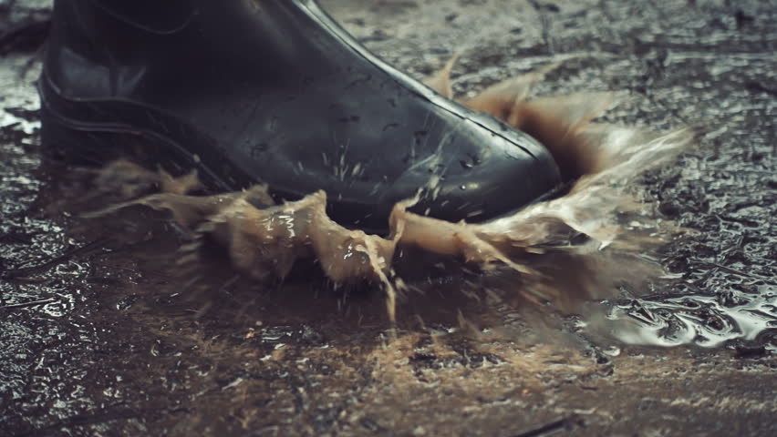 Black rubber boots step on a puddle and creates a splash which flies around. Slow motion, high speed camera, 250fps