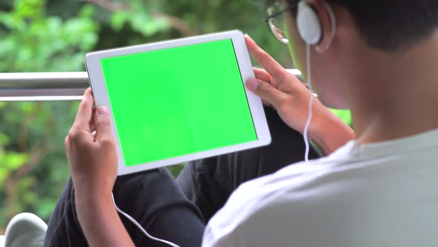Man Sits on chair Using Tablet PC Smart Phone Mobile Device in Nature with Green Screen and wearing headphones.