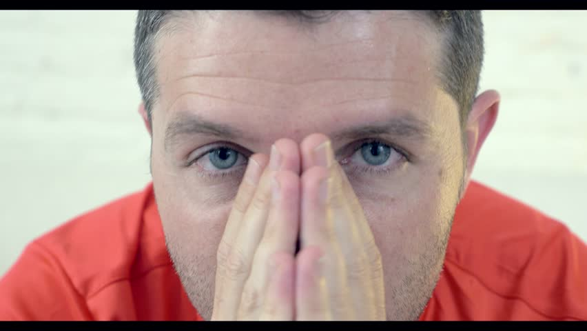 4k shot of close up face of man with blue eyes in stress and tension very nervous watching football on television suddenly celebrating crazy happy and ecstatic scoring goal in sport emotion concept