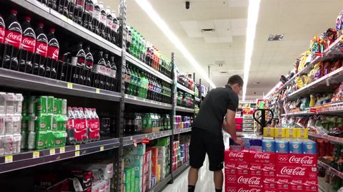 Burnaby, BC, Canada - July 11, 2016 : Grocery clerk stocking drink in Walmart store with 4k resolution