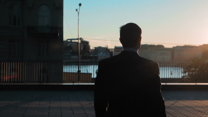 Silhouette of Young successful Businessman wins big deal with digital pad. Hands on. Outdoors on the business centre roof with city view. Slow motion shooting close-up. #18077086