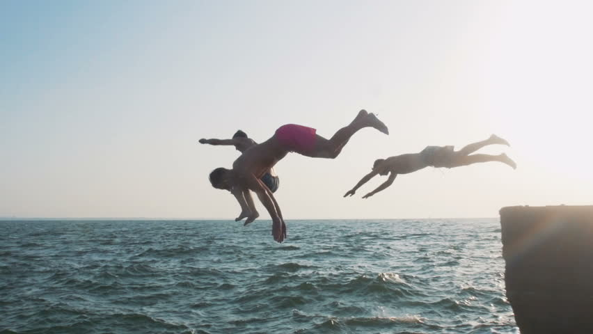 Group of friends running and jumping off sea pier in the water, slow motion | Shutterstock HD Video #18077266