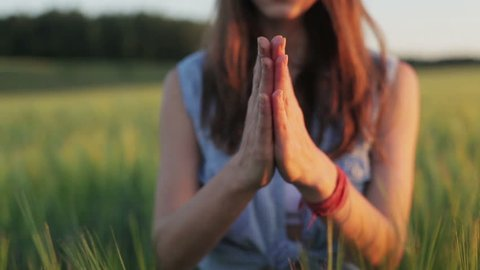 Young woman pray hands clasp outdoor summer sunset field close up. Unrecognizable girls palms together fingers focus country bright light color blur background. Religion faith yoga purity concept
