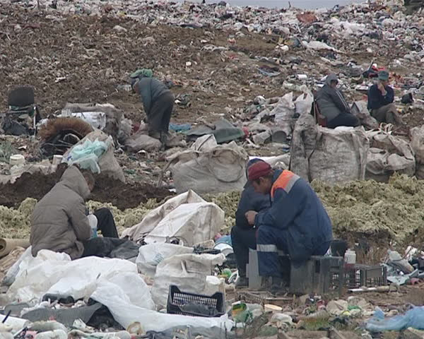 Dirty deprived homeless people and mountains of garbage in dump. Fight for survival. Environmental pollution. Poverty.