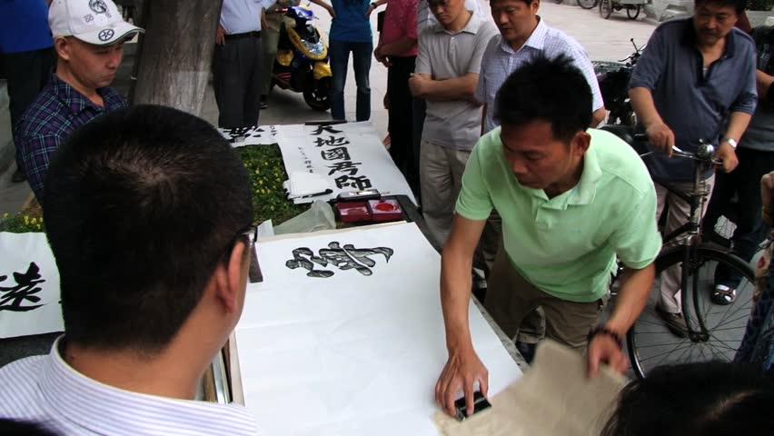 BEIJING, CHINA - MAY 27, 2013: Unidentified person performs calligraphy on paper at the street in Beijing, China. #18099316