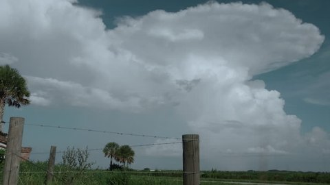 4K - Wide shot of pulse thunderstorm clouds over rural prairie land of the Florida wetlands.