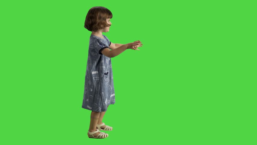 Little girl walking sideways over a green screen, happy and cheerful, spreading hands and laugh.