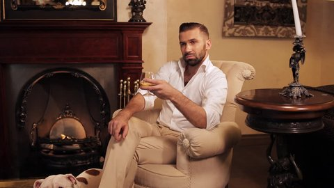 An aristocrat with a dog by the fireplace drinking whiskey. The comfort of home.
