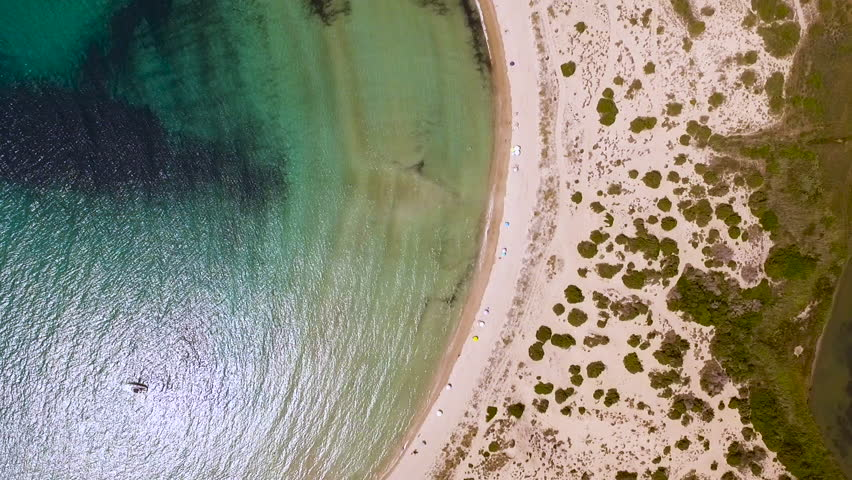Aerial view from the popular Voidokilia beach in Peloponnese, Greece. A half-moon-shaped beach surrounded by vivid water in an unrealistic way. Vertical angle in forward motion.