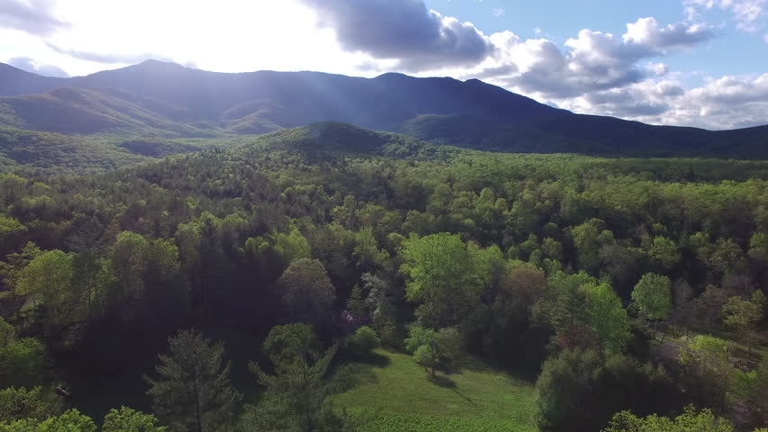 Aerial push of the Blue Ridge Mountains, sky, and surrounding forest in North Carolina. A cabin is seen in the lower half of the frame.