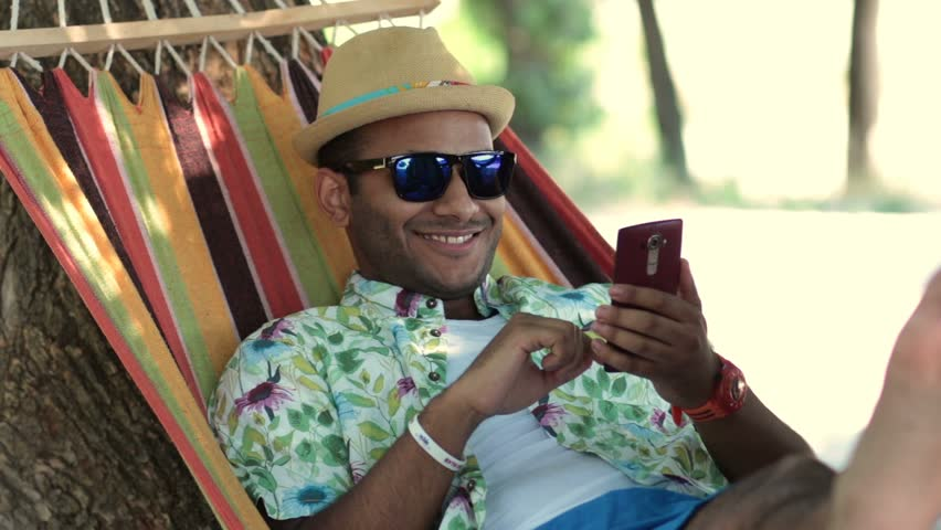 Young man swinging in a hammock while using phone