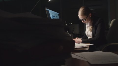 Tired young businesswoman analyzing financial statistics in dark office at night, taking off her glasses and trying to concentrate, shot on Sony NEX700 + Odyssey 7Q