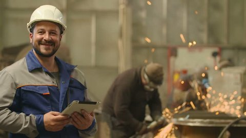 Engineer looks at camera, smile and shows his hand with thumb up in heavy industry factory