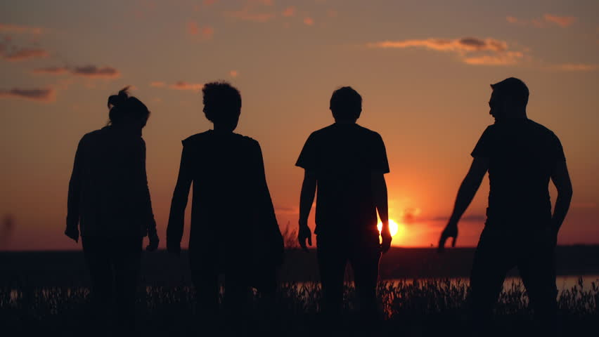 Silhouettes of young people have fun at sunset.