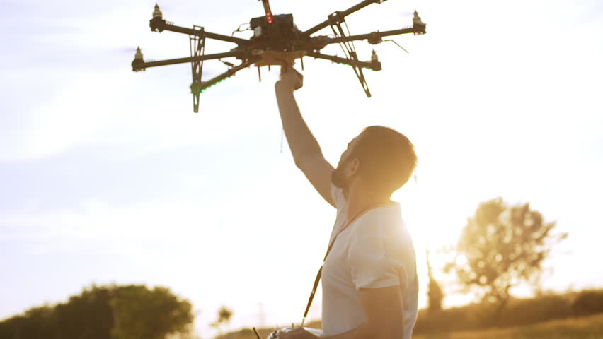 Young man controling drone in field at sunset. Slow motion Close up. #18198436
