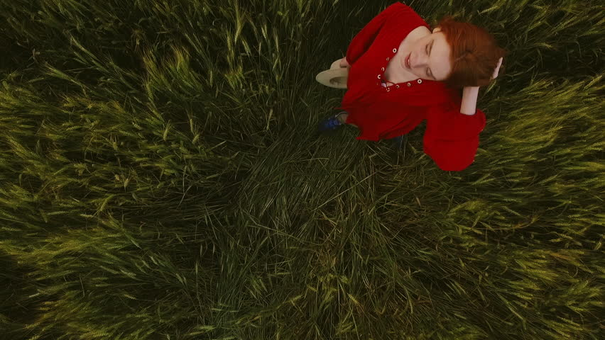 Young beautiful girl with foxy hair in red dress and hat walking in field. Slow motion. Aerial view. | Shutterstock HD Video #18200827