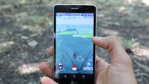 Sofia, Bulgaria - July 23, 2016: Man holds in his hand a mobile phone showing on screen Pokemon Go augmented reality mobile game. Playing in the park. Catching the Meowth pokemon.