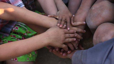 Many connecting children's hands. Mrauk-U, Myanmar. Burma