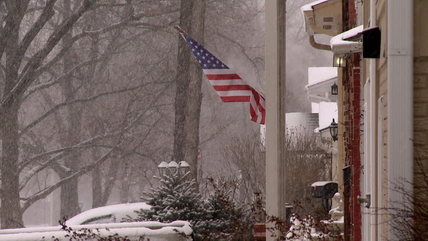 An American Flag In A Neighborhood During A Snowstorm. Patriotism In Bad  Weather.