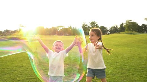 Huge soap bubbles playing bursting. Summer games with fresh air countryside. exciting Physics education Kids. dog brings a stick. Slow motion video footage. Contre-jour Backlight.  Flares flecks sun