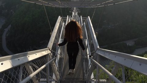 Young woman gracefully run downstairs, long hair curl on wind. POV camera follow behind. Narrow passage of modern suspended Skybridge crossing shaded canyon