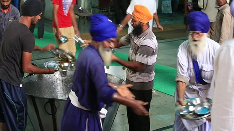 AMRITSAR, INDIA - SEPTEMBER 27, 2014: Unidentified poor indian people clean dishes at a soup kitchen in the Sikh Golden Temple