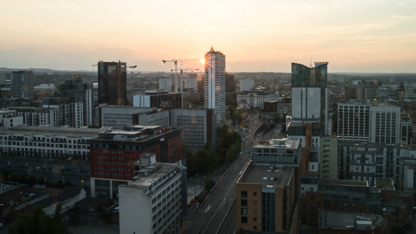 Birmingham, England skyline timelapse at sunset. Filmed at a high angle facing west with the Mailbox retail center in the foreground. 4K