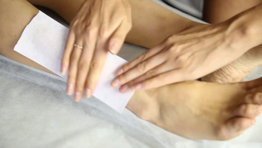 Women legs and hair removal with hot wax painful procedure. Woman In A Beauty Salon Doing Depilation. Wax depilation in a beauty salon