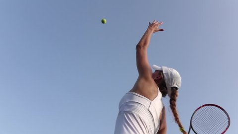 Girl serving tennis ball. Tennis player. Slow motion