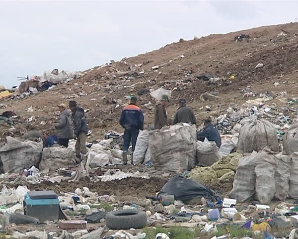 Many homeless people with full bags in dump surrounded by rubbish. Environmental pollution. Poverty.