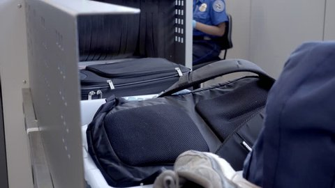 NEW YORK - JULY 1, 2016: baggage security check at JFK airport in 4K in NY. Conveyors transport personal items in trays across security points in American airports.