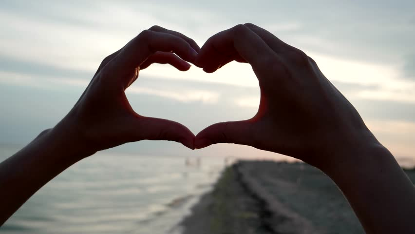 Hands show heart at sunset on the beach | Shutterstock HD Video #18372676